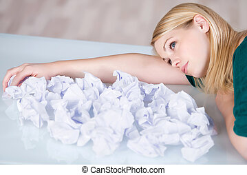 Businesswoman Relaxing With Paper Balls In Front At Desk -...