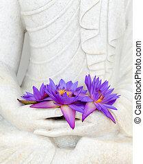 Fresh flowers in Buddha image hands
