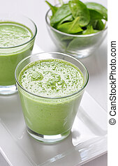 Spinach smoothies in glass on a wooden background