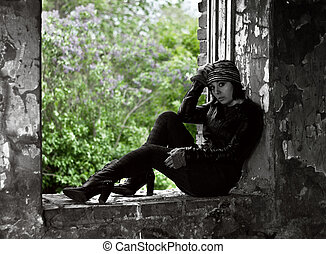 Woman in grunge style sitting on window with lil - Black and...