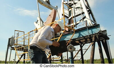 Man engineer with securities for the oil pumping unit