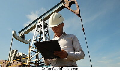 Man (engineer) with securities for the oil pumping unit