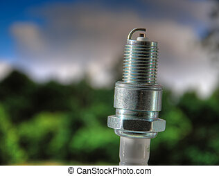 Spark plug against summer lanscape