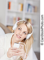 Woman Looking Up While Listening Music On Headphones - Young...
