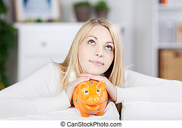 Young Thinking Woman Holding Orange Piggy Bank - Portrait of...
