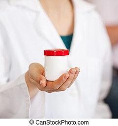 Female Pharmacist Holding Medicine Bottle - Mid section of...