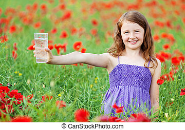 Smiling little child holding a glass of water in flower...