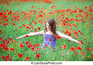 Young girl playing in a poppy field standing amongst the...