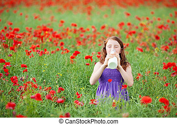 Young girl drinking milk in a poppy field - Young girl...