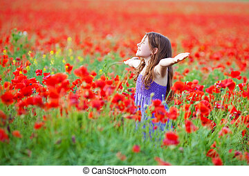 Cheerful young child enjoying the fresh air in flower field