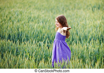 Young girl playing in a wheatfield dancing around with her...