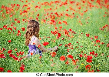 Girl in flower field - Young Caucasian girl picking a flower...