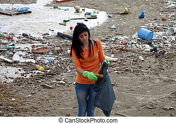 Young activist cleaning dirty beach in nature disaster -...