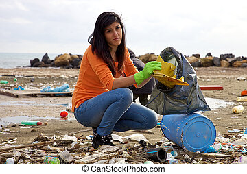 Young woman trying to clean dirty beach ecological disaster...