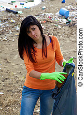 Young woman with bag full of dirt on destroyed dirty beach -...