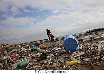 Young woman with bag trying to clean beach full of dump dirty and industrial mess
