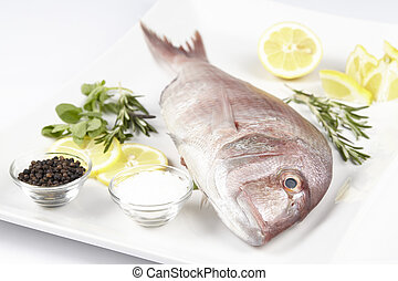 A red sea bream with spices, lemon slices and herbals - A...
