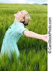 Cheerful woman enjoying the fresh air in cornfield