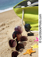 Beach time - Straw green bag and sunglasses on the sandy...