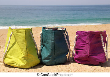 Vivid multicolored beach bags on the seashore - Three vivid...