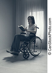 Young woman reading a book sitting on the wheelchair against...