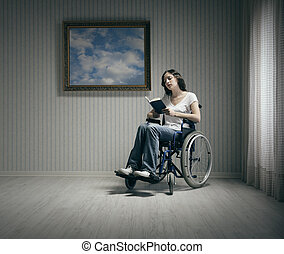 Disabled young woman reading in a wheelchair