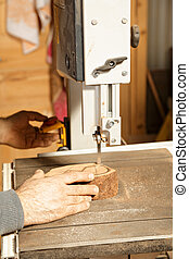 Artisan hands sawing billet at bandsaw while making pipe