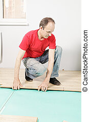 Guy in red installing flooring