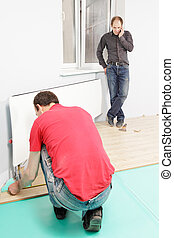 Men at work one installing flooring while other talking on...
