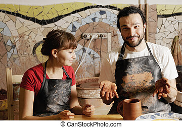 Potters with jug - Positive potters in workshop showing jug