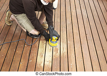 Mature man performing maintenance on home wooden deck -...