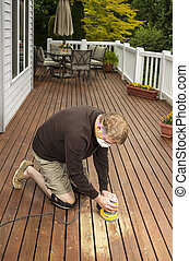 Mature man working on Natural Cedar Deck - Vertical photo of...