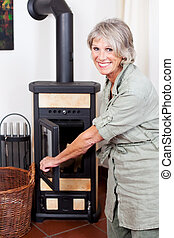 Senior lady puting wood in the stove