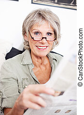 Retired woman reading a newspaper - Retired woman wearing...