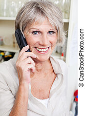 Smiling senior lady talking on a telephone - Smiling...