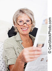Happy retired woman reading the newspaper - Happy grey...