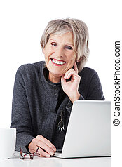 Happy senior woman with laptop and glassed on her table