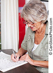 Elderly woman solving a crossword puzzle