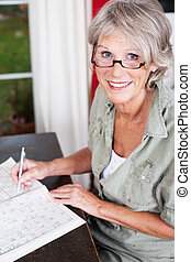 Older woman wearing glasses working on a crossword puzzle in...