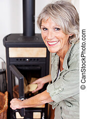 Senior woman putting logs in the woodburner - Senior woman...
