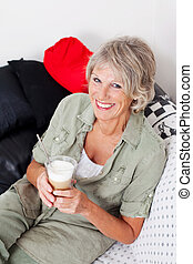 Smiling senior woman drinking cappuccino