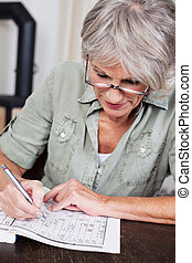 Senior woman completing a crossword puzzle - Senior woman...