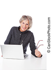 Modern senior woman using a laptop computer - Happy relaxed...