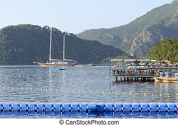 Yacht at the pier and outdoor restaurant on Mediterranean turkish resort, Marmaris, Turkey