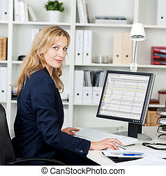 Mid Adult Businesswoman Using Computer At Desk - Side view...
