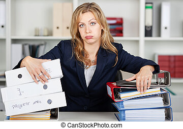 Bored Businesswoman Behind Stacked Binders At Desk -...