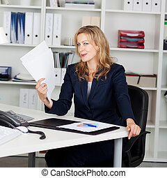 Businesswoman Fanning Herself With Documents - Mid adult...