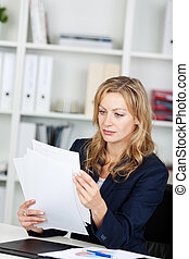 Businesswoman Reading Documents At Desk - Mid adult...