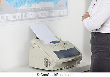 Businesswoman Wait For Fax - Midsection of businesswoman...