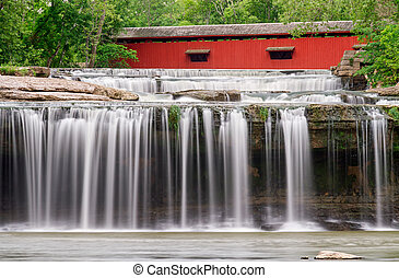 Waterfall and Covered Bridge - A red covered bridge spans...